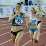 Grupo de mujeres corriendo en pista cubierta de atletismo