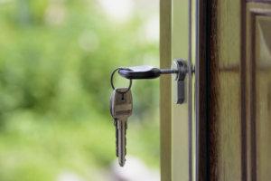 Llaves puestas en cerradura de puerta con fondo desenfocado de césped verde.